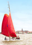 Red Sailboat, Volendam. Red Sailboat quits the harbor of Volendam, Netherlands stock photography