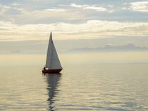 Red sailboat on Lake Constance Germany with Swiss Alps in the distance. A red sailboat with white sails on Lake Constance, Germany with the Swiss Alps and misty Royalty Free Stock Photography