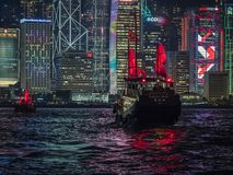 Red Sail Junk Boat on Victoria Harbour in Hong Kong. A red sailed junk boat sails in front of the neon covered buildings on the Victoria Harbour light show in stock photography