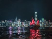 Red Sail Junk Boat on Victoria Harbour in Hong Kong. A red sailed junk boat sails in front of the neon covered buildings on the Victoria Harbour light show in stock photo