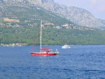 Red sailing boat, white boat, hills in the background. Picture taken at Adriatic sea in Peljesac channel, Croatia. There is a village in the background hills Royalty Free Stock Photos