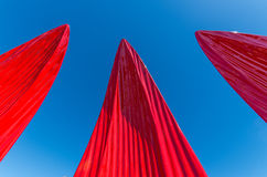 Red sails reaching towards the sky. Pointy red petals or sails reaching towards a clear blue sky stock photos