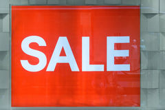 Red sale sign / banner inside window display. In a shopping mall Stock Photos