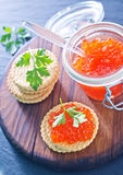 Red salmon caviar. In bank and on a table Royalty Free Stock Photography