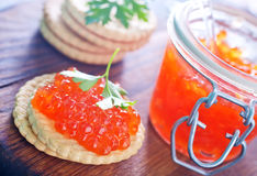Red salmon caviar. In bank and on a table Royalty Free Stock Images