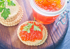 Red salmon caviar. In bank and on a table Stock Photos