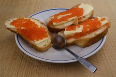 Red caviar in butter with bread. Red salmon caviar in oil with bread on a plate with a spoon on a wooden table Stock Photography