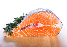 Red salmon fish with rosemary. Fresh salmon fish on wooden cooking desk Royalty Free Stock Photos