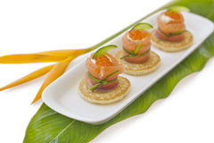 "Red salmon roll with chees, caviar and cucumber. On"" blinis"" base, on green leaf with tropical flower on the side Royalty Free Stock Images"