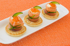 "Red salmon roll with chees, caviar and cucumber. On"" blinis"" base, on orange background Royalty Free Stock Photo"