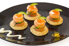 "Red salmon roll with cheese, caviar and cucumber. Red salmon rolls with cheese, caviar and cucumber on"" blinis"" base, on black plate Royalty Free Stock Photo"