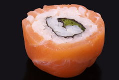 Red salmon sushi. Red salmon rolled up sushi on the black background Royalty Free Stock Photos