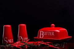 Red salt-cellar, pepper-box and butter on darck background by Cristina Arpentina Stock Photo