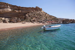 Red sand beach with boat, Rhodes Royalty Free Stock Photo