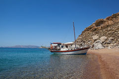 Red sand beach with ship, Rhodes Stock Photography