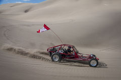 Red sand dune buggy racing by in the sand dunes Stock Image