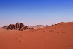 A red sand dune with a rock background in desert Stock Images