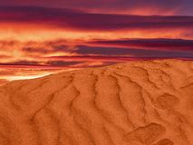 Red sand hill in the desert. ripples in the sand with the purple clouds stock image