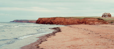 Red Sand Shores of Prince Edward Island. Sandstone cliffs and red sand beaches of Prince Edward Island with a lonely cottage up on top of a cliff Stock Images