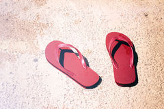 Red sandals on wet floor. Photograph of a pair of red sandals on a wet floor Stock Photos