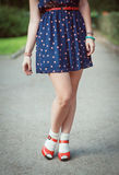 Red sandals with white socks on girl legs in fifties style. Outdoor Stock Image