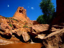 Red sandstone tower with stream and waterfall in Coyote Gulch canyon in Escalante, Utah Royalty Free Stock Photography