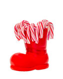 Red Santa Claus boots with colored sweet lollipops, candies, shoes with Merry Christmas yellow sparkly write. Saint Nicholas boots Royalty Free Stock Photo