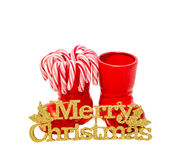 Red Santa Claus boots with colored sweet lollipops, candies, shoes with Merry Christmas yellow sparkly write. Saint Nicholas boots Stock Image
