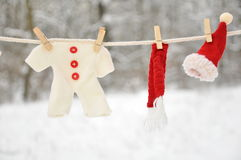 Red santa claus clothes drying. In the open air hanging on clothes line affixed with wooden pegs Royalty Free Stock Photos
