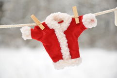 Red santa claus clothes drying. In the open air hanging on clothes line affixed with wooden pegs Stock Photography