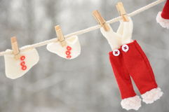 Red santa claus clothes drying. In the open air hanging on clothes line affixed with wooden pegs Royalty Free Stock Photo
