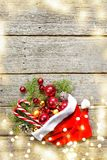 Red santa claus hat with christmas composition balls, toys, candy, fir branches on vintage wooden background Stock Photos