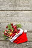 Red santa claus hat with christmas composition balls, toys, candy, fir branches on vintage wooden background royalty free stock photos