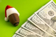 A red Santa Claus hat is dressed on a souvenir American football or rugby ball next to dollars on a green background. Christmas stock image