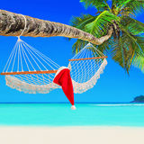 Red Santa Claus hat on hammock at palm island beach Stock Photos