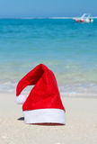 Red Santa Claus hat on ocean background. Red hat of Santa Claus on the island beach with blue ocean waves on background Royalty Free Stock Photo