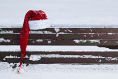 Red Santa Claus hat on snow covered bench. Outdoors Stock Image