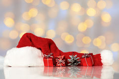 Red santa claus hats with gifts on colorful background Royalty Free Stock Images