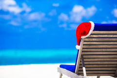 Red santa hat on beach longue at tropical resort Stock Photos