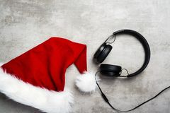 Red santa hat and a headset on a gray concrete table. Red santa hat and a black headset on a gray concrete table stock photo