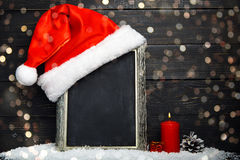 Red Santa hat on the chalkboard with snow Stock Images