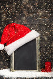 Red Santa hat on the chalkboard with snow Stock Image