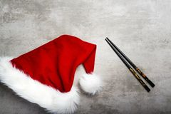 Red santa hat and chopsticks on a gray concrete table stock images