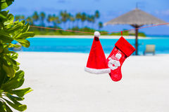 Red Santa hat and Christmas stocking on the beach Royalty Free Stock Photography