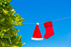 Red Santa hat and Christmas stocking between palm Stock Photo
