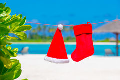 Red Santa hat and Christmas stocking between palm trees on white beach Stock Photography