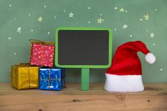 Red Santa hat with colorful gift box on wooden floorand. Merry christmas Happy new year. Red Santa hat with colorful gift box on wooden floorand and scene green Stock Images