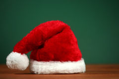 Red Santa Hat With Copy Space on Green and Wood Background Royalty Free Stock Images