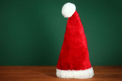 Red Santa Hat With Copy Space on Green and Wood Background Stock Image