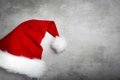 Red santa hat on a gray concrete table. Red santa hat with white fur on a gray concrete table royalty free stock images